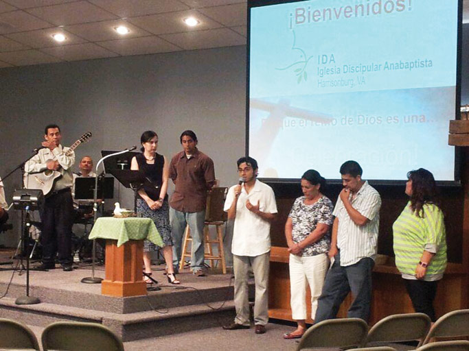 Standing with a local Latino family during a summer IDA gathering, Jossimar Diaz-Castro speaks about spiritual enrichment and immigrant rights. Courtesy of author