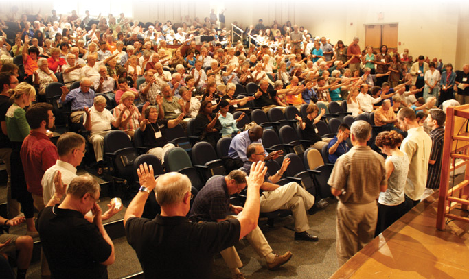 Participants reach out in a prayer of blessing for those commissioned for service Friday evening. Photo: Jon Trotter