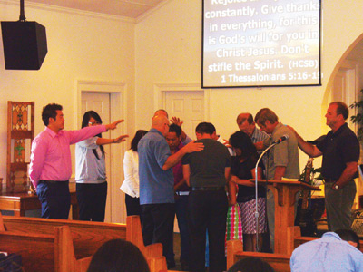 Members of the Hickory Hmong church, as well as district and conference representatives, pray for Jonah and Memee and their family and ministry. Photo: Susan Myer