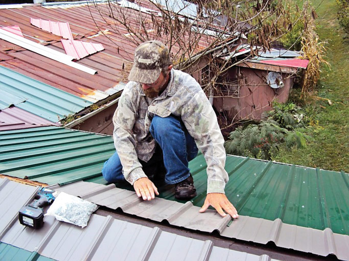 A member of the Grace Mennonite team works on a new metal roof. Photo courtesy of Karin King