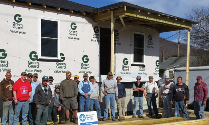 The new home build, along with a large volunteer framing group, for  the Rex family in Rainelle, West Virginia. The home owner is on the  left hand side. Photo by Rod Burkholder