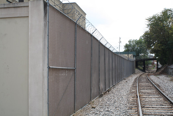 The jail wall and fence, hidden from view of the main streets.