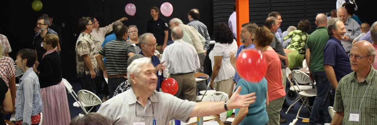 Delegates engage in a team-building balloon exercise at Conference Assembly