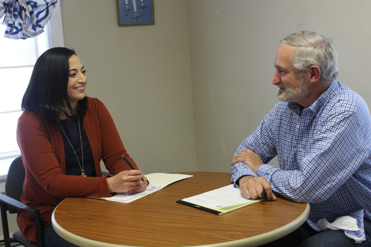 Faith In Action staffer Art Stoltzfus confers with Nadia Dames of Mt. Crawford, FIA campaign chair for housing.