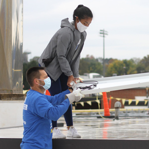 Eastern Mennonite School student Rahel Lema '21 and Paul Leaman, Head of School, work together during the EMS solar barnraising on October 10, 2020. See article on page 3. Photo by Andrea Wenger